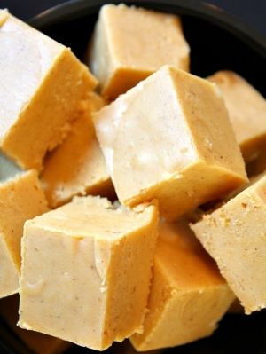 Pumpkin Fudge  3 cups sugar $ 3/4 cup melted butter $ 2/3 cup evaporated milk 1/2 cup canned pumpkin 2 tablespoons corn syrup 1 teaspoon pumpkin pie spice 1 (12-ounce) package white chocolate morsels 1 (7-ounce) jar marshmallow crème 1 cup chopped pecans, toasted 1 teaspoon vanilla extract