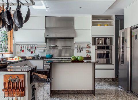 Uma vez abertas as portas de correr, enxerga-se a cozinha desde a sala de estar, com as panelas e os utensílios à mostra. Ampla, traz ilha central e móveis planejados, bancadas de granito café imperial e piso de granito do tipo arabesco. Projeto da arquiteta Cristina Xavier.
