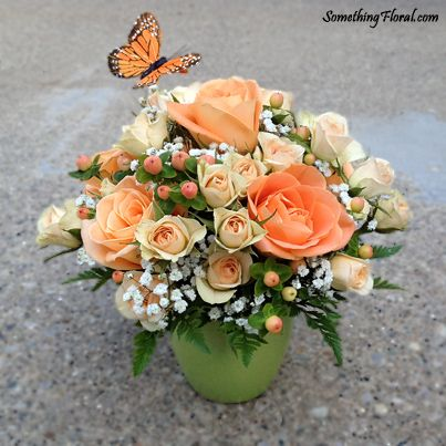 Peach, coral, green, and white centerpiece featuring roses, spray roses, hypericum berries, baby's breath, and accented with a faux butterfly. These centerpieces were created for a wedding, but the style would also be perfect for a bridal shower or engagement party.