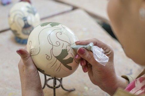 A woman paints an ostrich egg for an Azraq community project.
