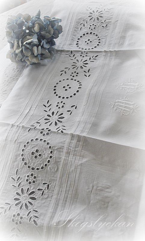 Broderie anglaise, pintucks, monogram. Looks like a bedsheet.