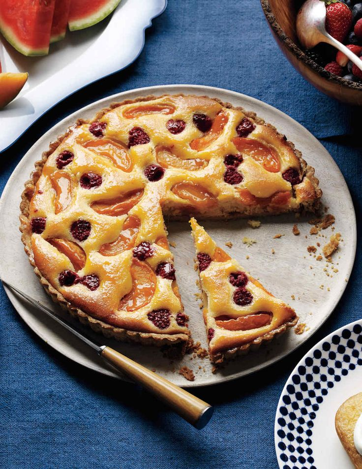 A custardy almond filling is studded with jewel-like fresh apricots and raspberries in this showstopping tart. It's best eaten the day it's made.