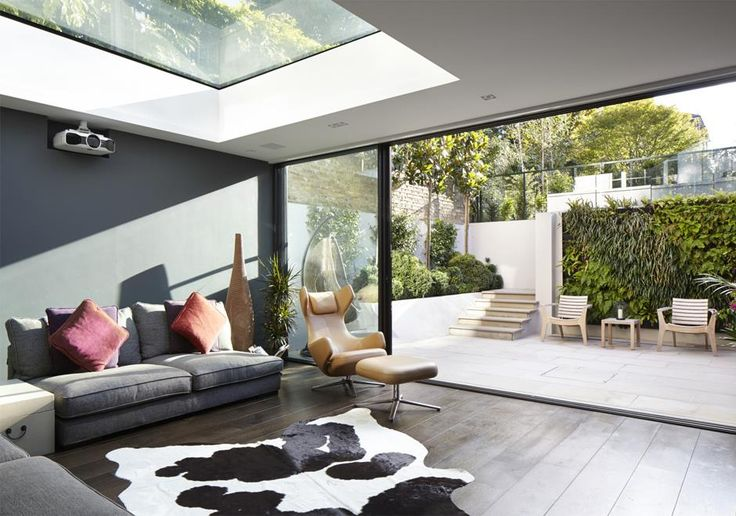 The living room in our Richmond basement and house extension can be opened up to the garden with large glass sliding doors or closed in in colder months. The walk on roof light means that the room will always be bright even with the dark grey wall finish.