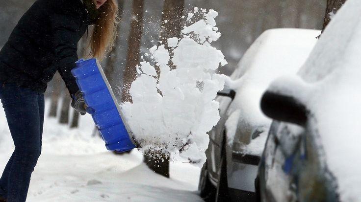 Frau räumt Schnee mit blauer Schneeschaufel   Bild: picture-alliance/dpa
