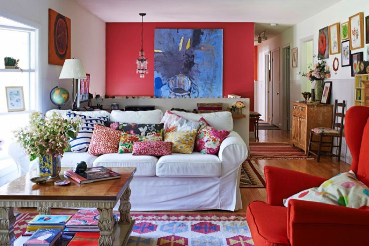 Living room: a white sofa is brightened with colorful textiles. I love the coffee table.