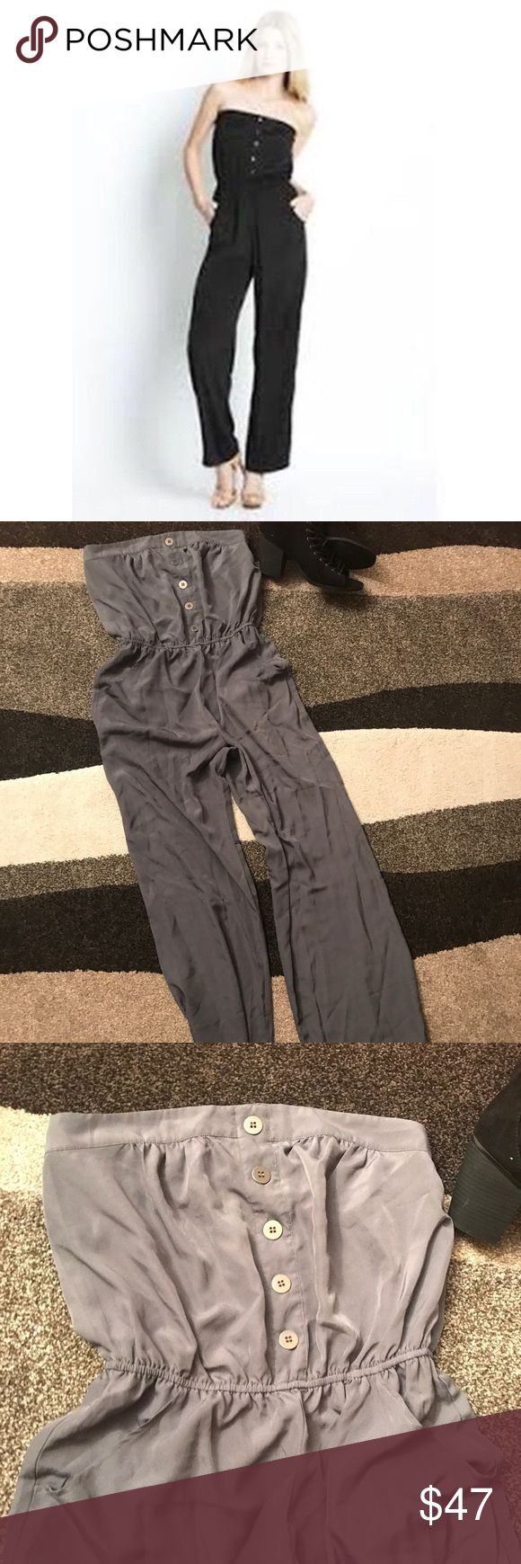 WALTER by Walter Baker: Pocketed Button Jumpsuit It's always fun to look feel beautiful and to make it look effortless.  This easy jumpsuit by Walter Baker does just that.   The elastic top prevents the slipping that is common with most dresses and jumpsuits and the tailored, elastic waist also gives the body a naturally proportioned shape.   Features two pockets in the front and a bonus stylish pocket in back.  Pair with a loose cardigan, a Moto jacket, or even a cropped sweater or bolero…