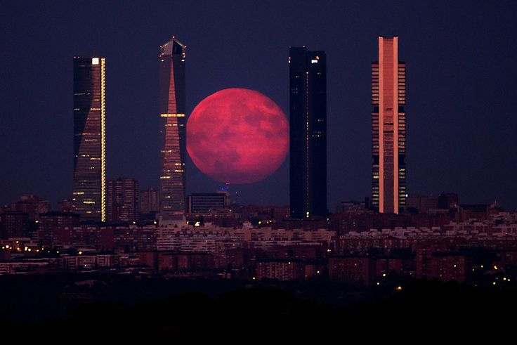 The moon shines through the Four Towers Madrid skyscrapers on Aug. 11, in Madrid, Spain. Gonzalo Arroyo Moreno / Getty Images