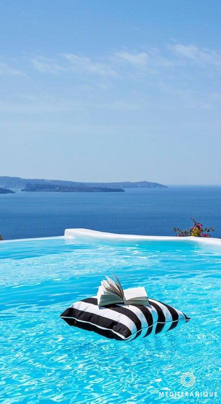 Views over the infinity pool and onto the cobalt blue sea and volcano from Canaves Oia in Santorini