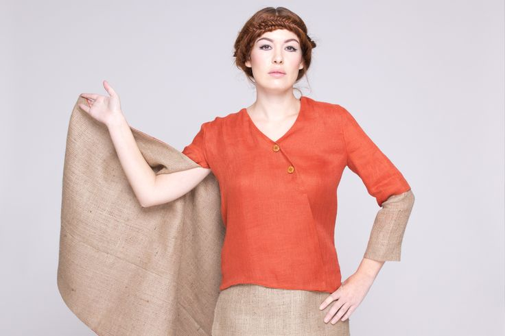 Enveloping cape with asymmetric sleeves made from rustic jute and linen.