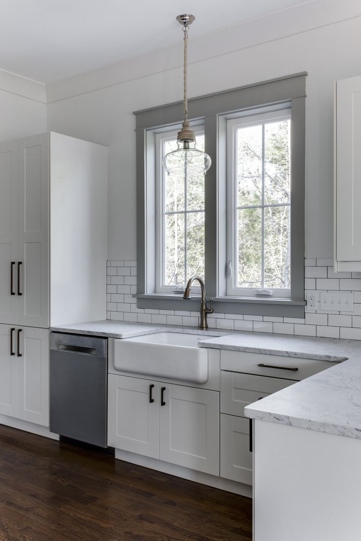Love the white cabinets, farmhouse sink and gray painted window trim in this kitchen. Barrow Building Group