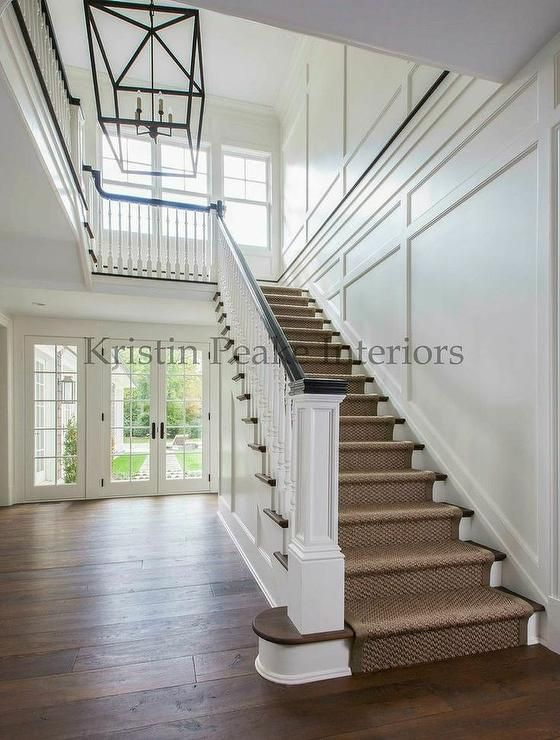 Transitional two story foyer features a lantern illuminating a staircase lined with a bound sisal ...