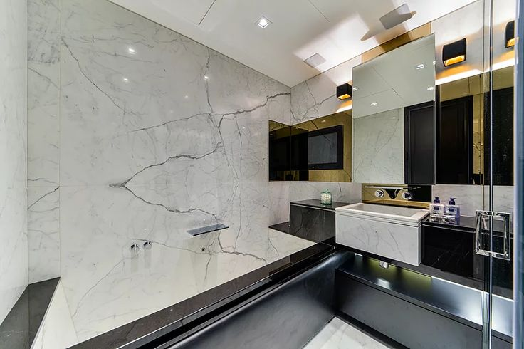 Calcutta Oro marble bathroom fitted with waterproof TV by Macassar Properties - London investment and development company