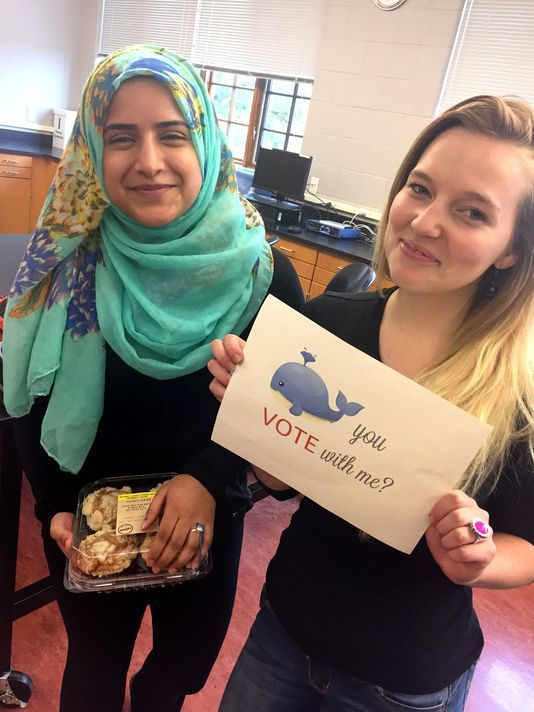 Asia Mian (left) receives a pollposal, a ring and package of blueberry muffins from Bryce Ohly. The two Mount Mary University students made a pact to vote next month in their first presidential election.  Mount Mary University
