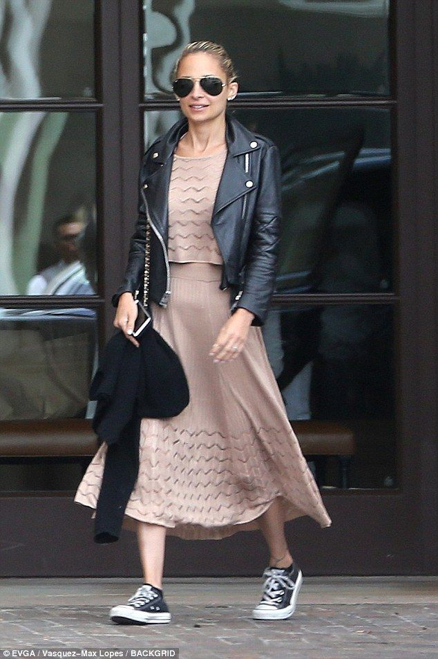 Cool: Nicole wore a champagne pink textured crop top with a matching high-waisted skirt and black Converse low tops, staving off the unseasonably cooler air with a black leather jacket
