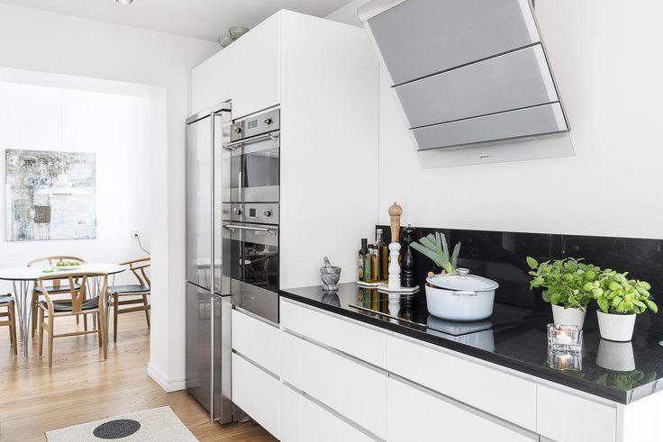 Påkostat kök från Ballingslöv där vita högblanka luckor med integrerade handtag går i snygg kontrast mot mörk bänkskiva i granit som även löper upp en bit på väggen.