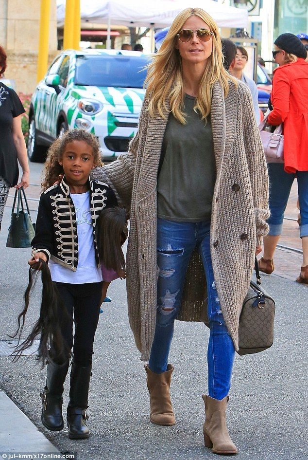 Mini fashionista: Little Lou, who carried her American Girl doll and extra strands of hair for the toy, appeared to bechannelling the late Michael Jackson's military look in a black jacket with gold trim