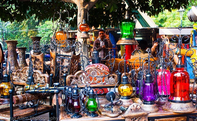 """Delhi Haat, New Delhi.   Dilli Haat market at night.  For the most authentic and down-to-earth shopping experience. Modeled around a traditional rural marketplace (a """"haat""""), it features some 200 individual stalls that form a permanent al-fresco arts-and-crafts bazaar.  This is a great place to buy original hand-made items directly from the producers themselves, with artisans from across the country selling everything from panel-beaten silver jewellry..."""