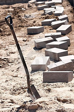 A background of a shovel and bricks for construction.