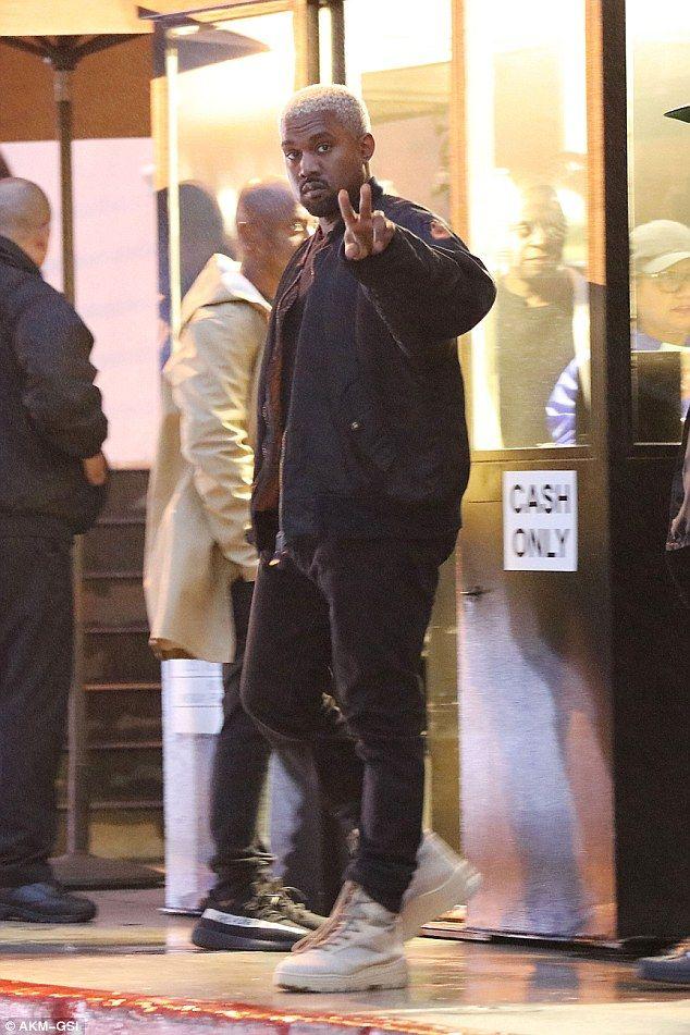 Good spirits: Kanye flashed the peace sign while exitingBandera Restaurant