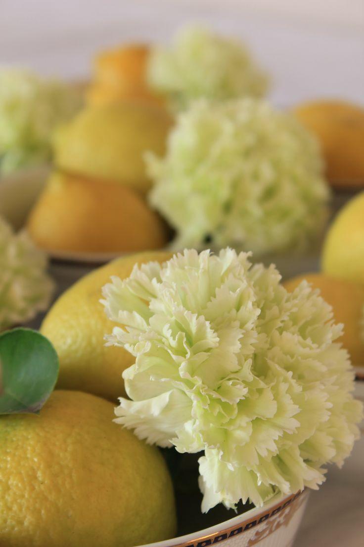 Limoni e garofani per centrotavola eleganti e inediti: mettere poca acqua e incidere la buccia dei limoni