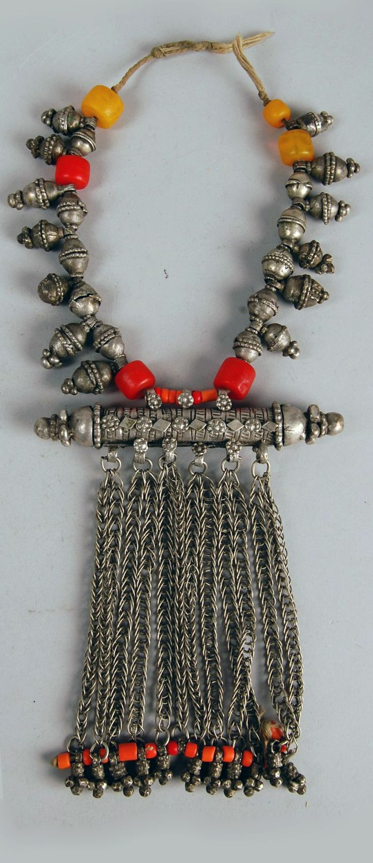 Yemen ~ Razih | Silver necklace of plain bobbles (xaTrah/xaTaayir) and knobbed bobbles (zirri/zurarah) and red and yellow beads, with amulet-case (Harz) with chains and orange beads pendant from it. | 20th century, acquired by the British Museum in 1993.