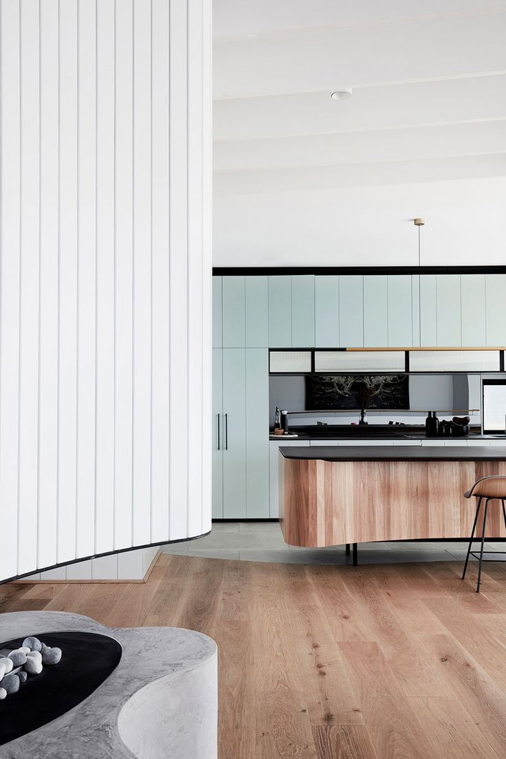 In this modern kitchen, light blue cabinetry by Building With Options has been combined with a reconstituted stone benchtop and an island covered with vertical wood pieces. #ModernKitchen