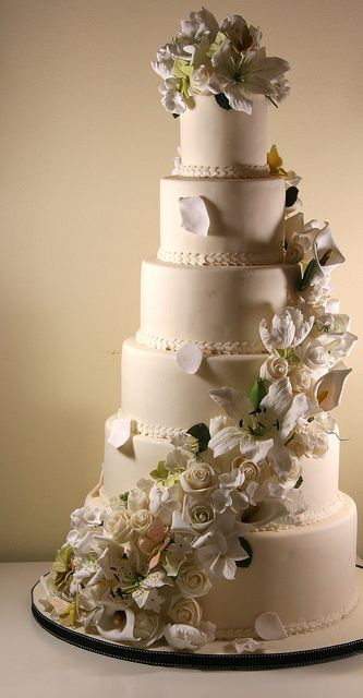 Six-tier wedding cake with sugar flowers cascade by Elizabeth's Cake Emporium. Flowers include roses, casablanca lilies, arum lilies, sweet peas, hydrangeas, parrot tulips and assorted buds and greenery.