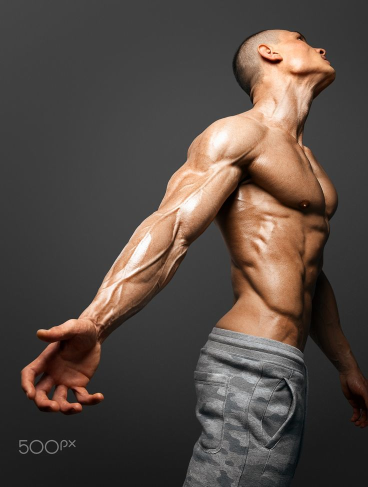 Strong Athletic Man Fitness Model - Bodybuilders hand and arm with veins protruding from under the thin skin. isolated on black background with clipping path