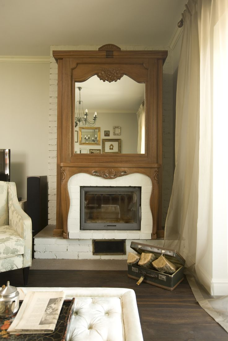 wood sculpted decorative fireplace with mirror, wodden fireplace, quilted coffee table, floral armchair, pastel interior