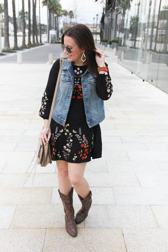 Houston Style Blogger wears a country music festival outfit including a floral embroidered dress with a denim vest and cowboy boots.