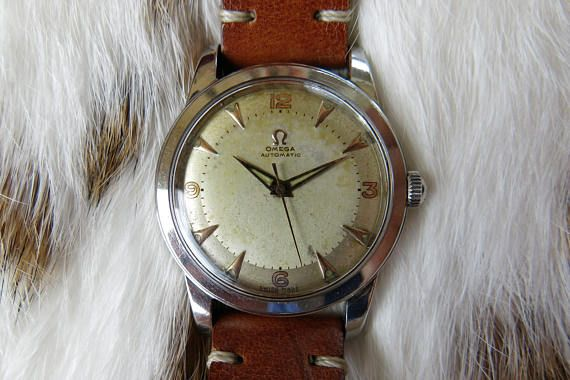 Vintage OMEGA automatic bumper 350 caliber stainless steel mens watch The watch dates from the 1940s. It is in overall great condition. The dial has a nice patina, with pink golden indexes and numbers. OMEGA AUTOMATIC is printed at 12 oclock under the Omega logo. SWISS MADE is