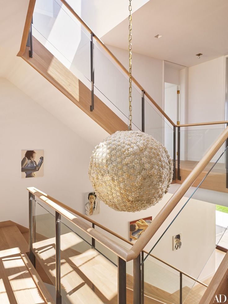A vintage Murano-glass pendant light illuminates the central staircase of this Hamptons home, designed by architect Annabelle Selldorf and designer Joe Nahem. | archdigest.com