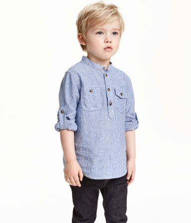 Collarless shirt in a cotton and linen blend with a small stand-up collar. Short button placket, chest pockets with button, and long sleeves with roll-up tab and button.