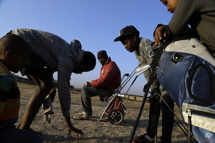 Wynand Morudu, center, watches as children count golf balls during their game at a park in Katlehong township, east of Johannesburg, South Africa, Thursday, July 16, 2015. (AP Photo/Themba Hadebe)