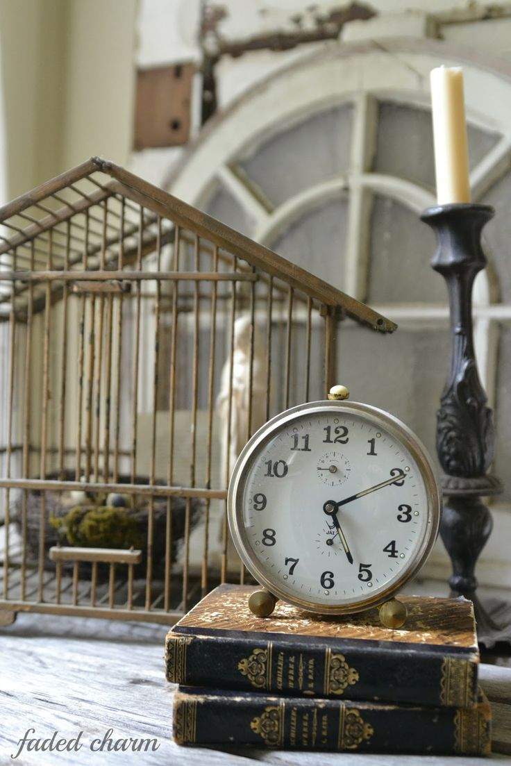 Vignette with vintage bird house, books and clock
