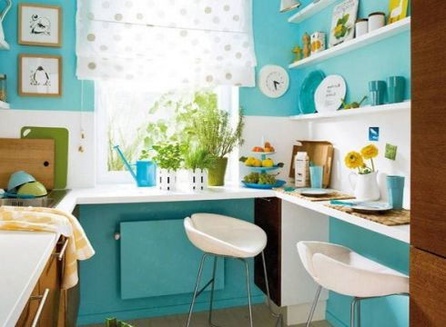 Kuchnia, gdzie dominuje ulubiony kolor - turkus. Reszta dodatków w bieli - plus fantastyczna roleta w kropki. Klimat podkręcają zielone rośliny i drewniane wykończenie.