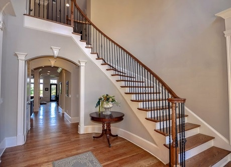 This classic staircase winds gracefully above arches framed by pillars. The  New Canaan model from