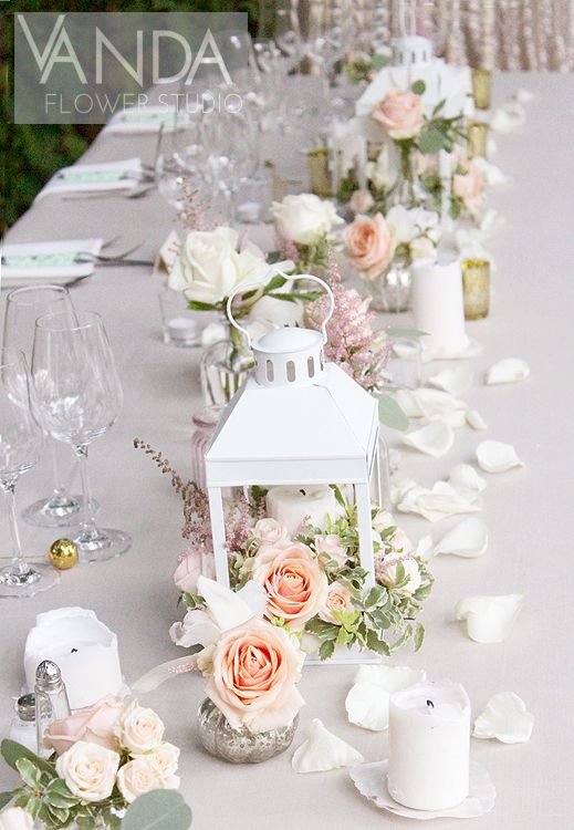 Romantic white lanterns filled with Roses and Orchids decorate the wedding top table, in between cream candles, tealight votives, and eclectic vases filled with the same.