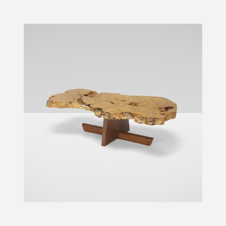 Lot 122: George Nakashima. Minguren I coffee table. 1986, maple burl, American black walnut. 53½ w x 28 d x 15¼ h in. estimate: $70,000–90,000. George Nakashima hand-selected this special, figured tabletop at the request of the original owners. The expressive and unusually thick slab top displays numerous fissures, recesses, burls, knots, continuous free edge and a naturally formed 'bridge' to one edge. The light-colored and sculptural tabletop stands in balanced contrast to the mini...