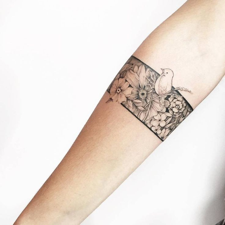 Floral armband tattoo on the right forearm.