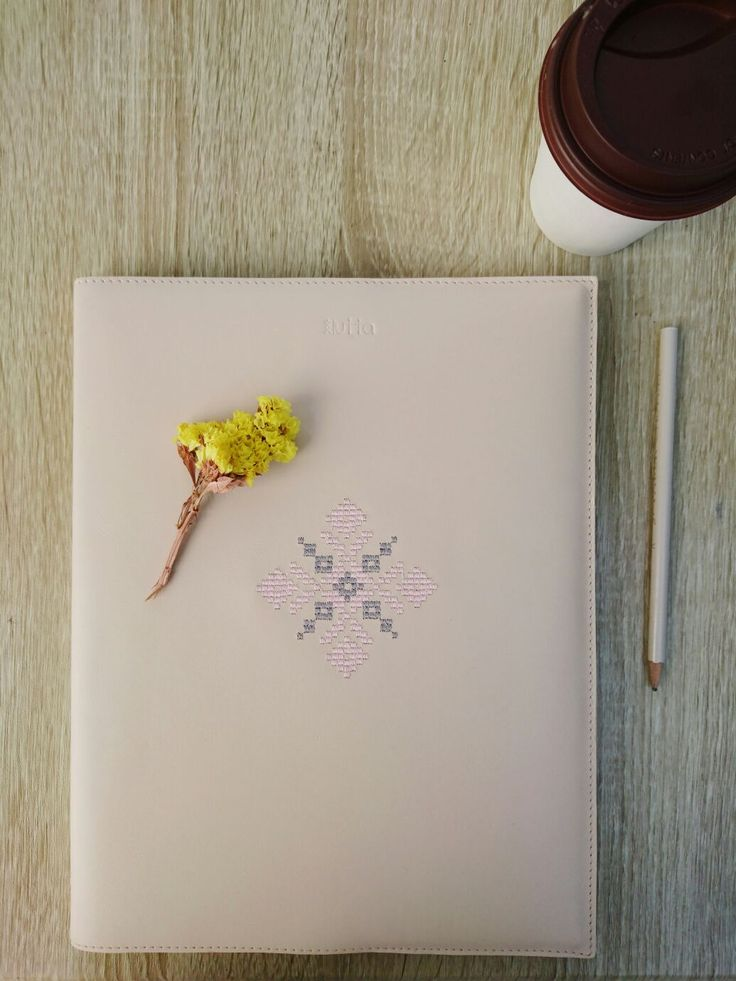 Leatherbound notebook and planner in a flat lay photo. Coffee and Farber Castle pencil. Yellow flowers.