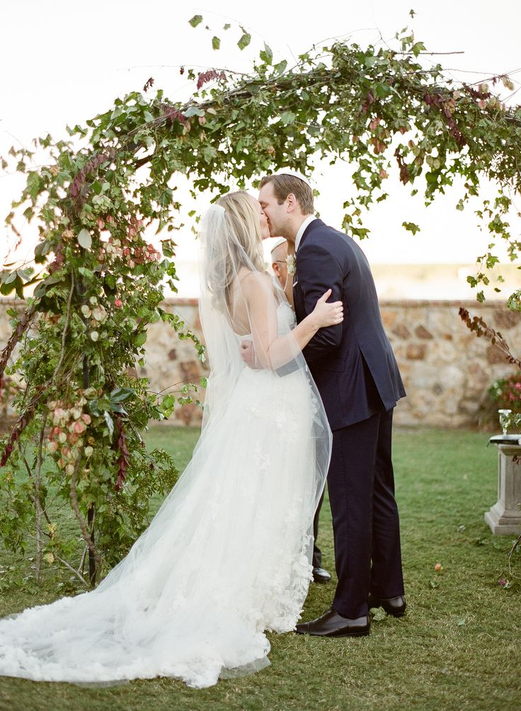 sealed with a kiss under their large wedding arch of loose and organic foraged elm, oak and magnolia branches, vines, plum branches, fern and faded raintree blossoms at bella collina.