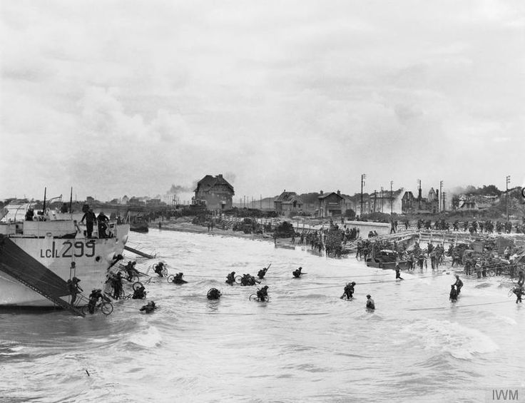 Bernières-sur-Mer, Juno Beach; Canadian troops come ashore at Bernières-sur-Mer on Juno Beach, 6 June 1944. This photograph shows how the incoming tide reduced the width of beach to only a few yards, which meant that it was soon clogged by vehicles and equipment. The initial landings on the coast of Normandy went well, and overall casualties were lighter than expected, but failure to take the strategically vital town of Caen on the first day was a major setback.