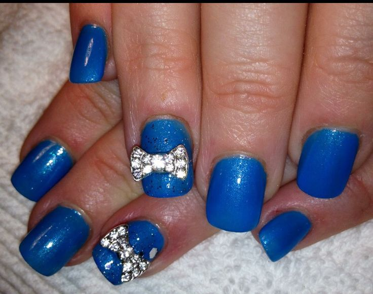 Blue polished acrylic nails with bows.