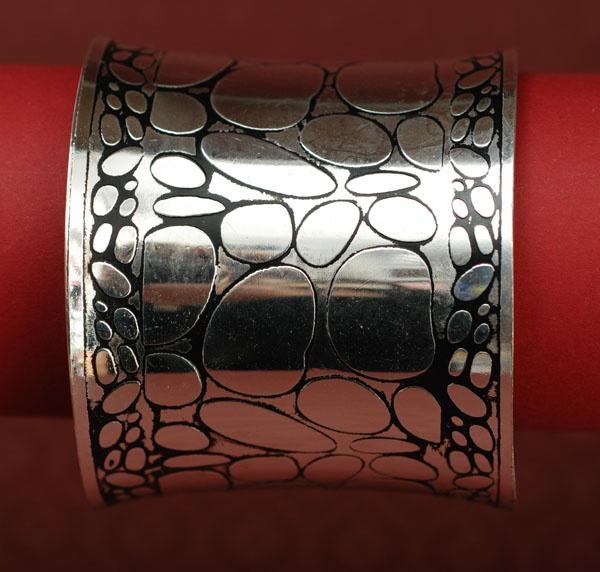 Szeroka, efektowna bransoleta w kolorze srebrnym.
