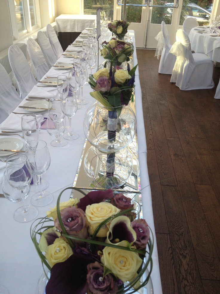 Top Table Display, Brides and Bridesmaids Bouquets placed in vases with coiled wire linking each vase