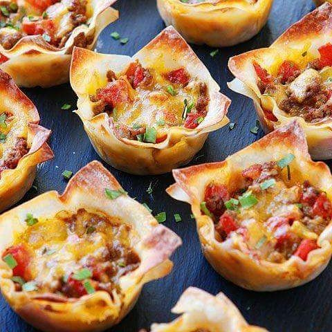 Crunchy Taco Cups  - 1 lb lean ground beef, browned and drained 1 envelope (3 tablespoons) taco seasoning 1 (10-oz) can Ro-Tel Diced Tomatoes and Green Chiles 1½ cups sharp cheddar cheese, shredded (or Mexican blend) 24 wonton wrappers - Method: kevinandamanda.com