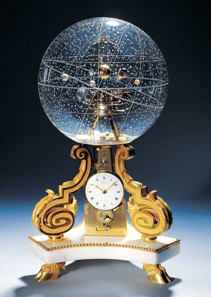This is called Pendulette de table avec Planetarium (Planetarium Table Clock). It keeps time. AND, the earth rotates around the sun in perfect real time. AND, the other nine planets rotate as well, around, up, down in relation to the etched constellations of precisely positioned stars on the crystal globe. Made in Paris in 1770.