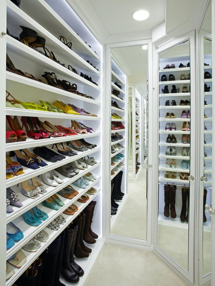 A narrow walk in closet incorporates built in angled white for Walk in shoe closet