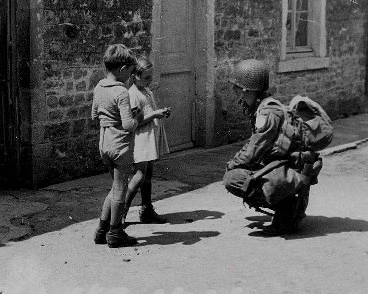 An American paratrooper gives two French children gum on June 8, 1944